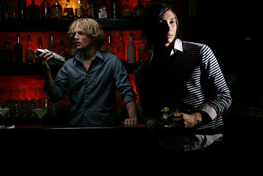 Two men at a bar, bartender and patron : Stock Photo