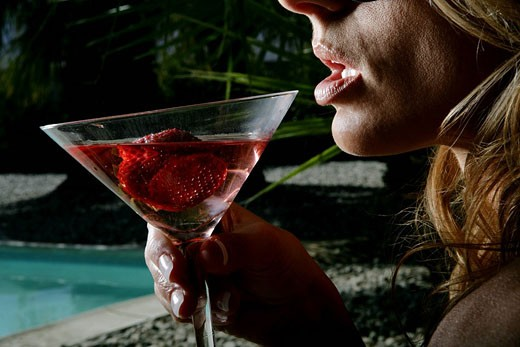 female drinking cocktail at poolside : Stock Photo