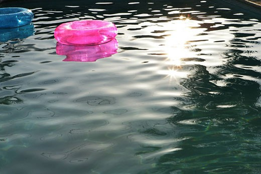 Stock Photo: 1742-12485 Pink and blue innertubes floating in water