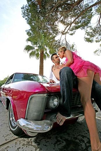 Woman seducing a man on a car hood : Stock Photo