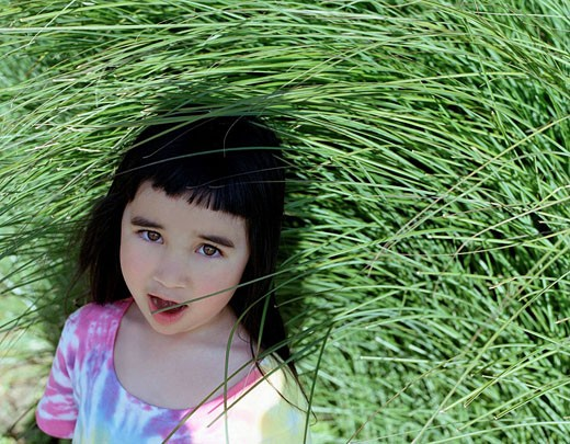 Asian girl standing in grass. : Stock Photo