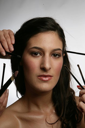 Stock Photo: 1742-13319 Young woman with make_up brushes, studio shot.