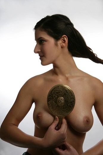 Young nude woman holding mirror, studio shot. : Stock Photo