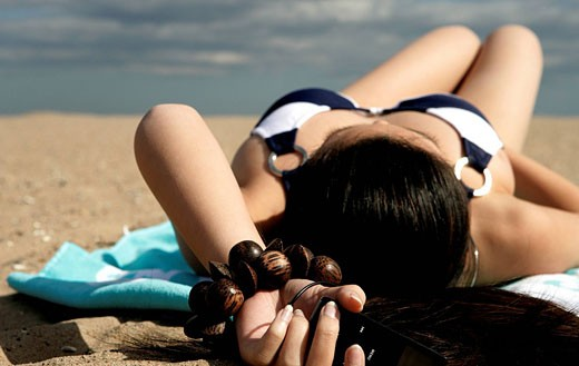 View of a young woman relaxing on a beach. : Stock Photo