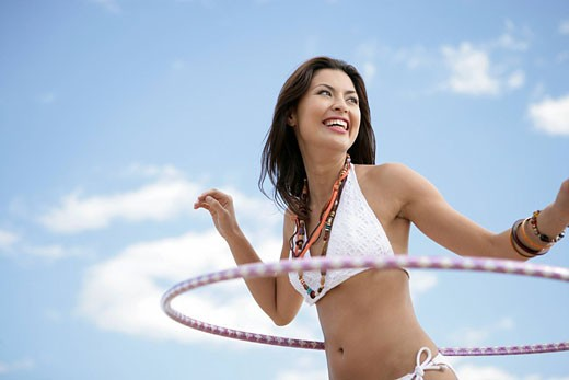 View of a woman doing a hula_hoop. : Stock Photo