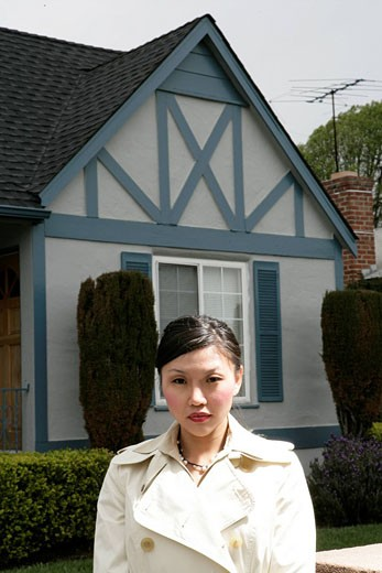 View of a young woman standing in front of a house. : Stock Photo