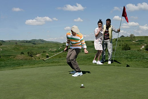 Stock Photo: 1742R-1166 View of people rejoicing on a golf course.