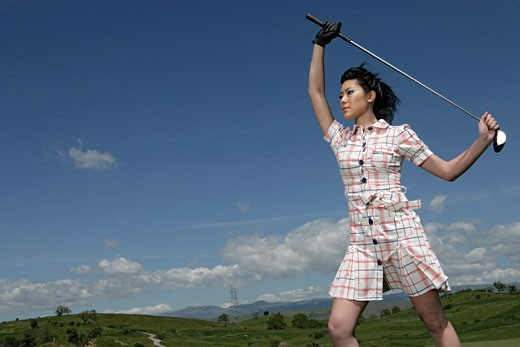 Woman posing with a golf club. : Stock Photo