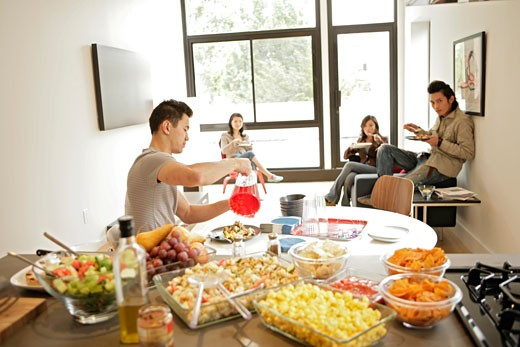 Four people having their meal, side view : Stock Photo