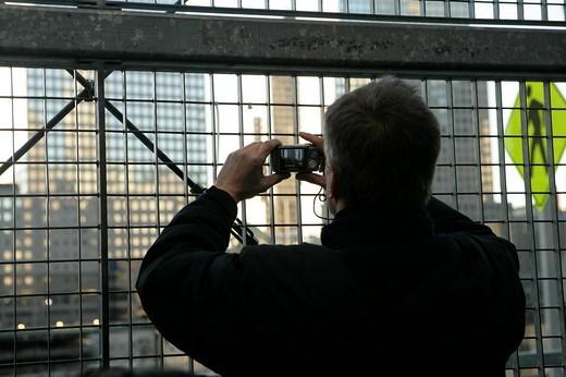 Man taking photo thru fence, rear view : Stock Photo