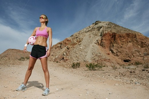 Woman in the desert holding a soccer ball : Stock Photo