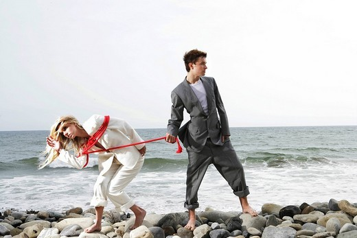 Young businesswoman bound in red rope captured by businessman on beach : Stock Photo