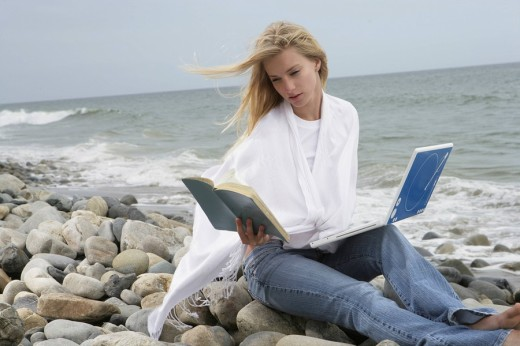 Stock Photo: 1742R-13735 Young woman on beach with book and laptop