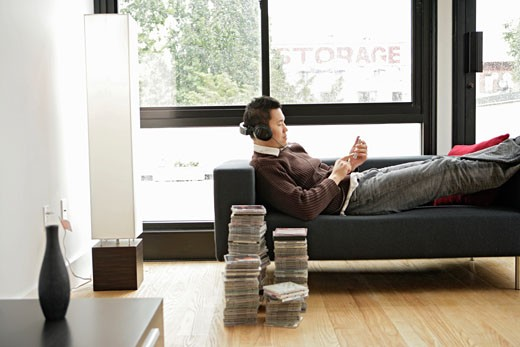Stock Photo: 1742R-1374 Young man listening to music, side view