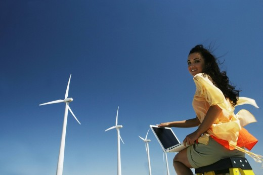 Young woman sitting on ladder with laptop near wind farm. : Stock Photo
