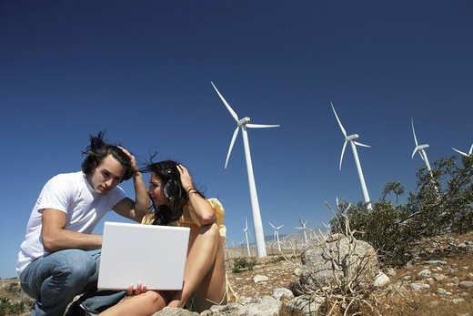 Young couple with laptop sitting near wind turbines. : Stock Photo