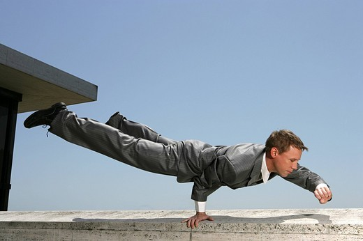 Businessman balancing on one hand on a ledge : Stock Photo