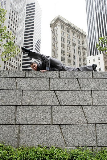 Portrait of acrobatic businessman doing split on wall in city : Stock Photo