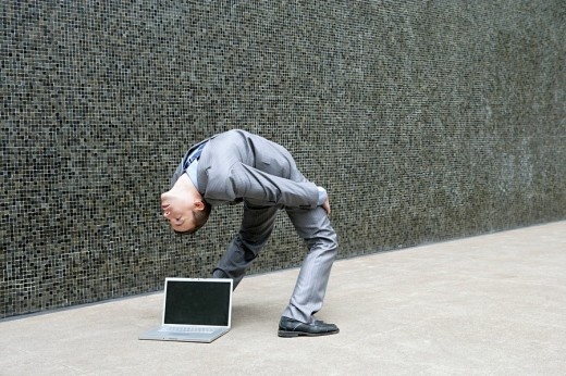 Young businessman with laptop bending over backwards : Stock Photo