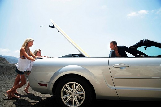 Stock Photo: 1742R-14182 Identical twins pushing brokedown convertible on side of road with man in driver´s seat