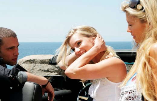 Stock Photo: 1742R-14213 Young man flirting with identical twins sitting in convertible