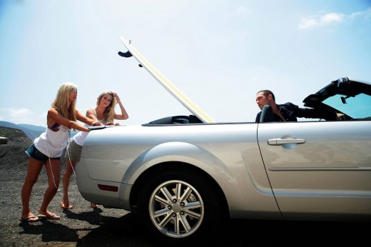 Identical twins pushing brokedown convertible on side of road with man in driver´s seat : Stock Photo