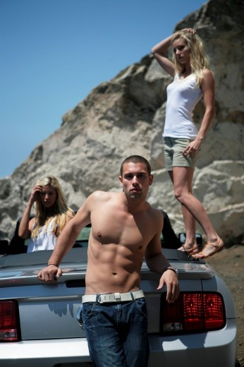Sexy young man leaning against convertible with identical twins in background : Stock Photo