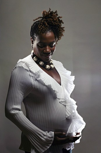 Portrait of pregnant African American woman, studio shot : Stock Photo