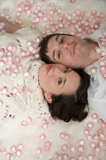 High angle view of young couple lying down amongst scattered candy mints : Stock Photo