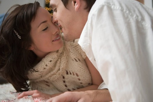 Stock Photo: 1742R-14642 Young couple kissing on floor of home at Christmas