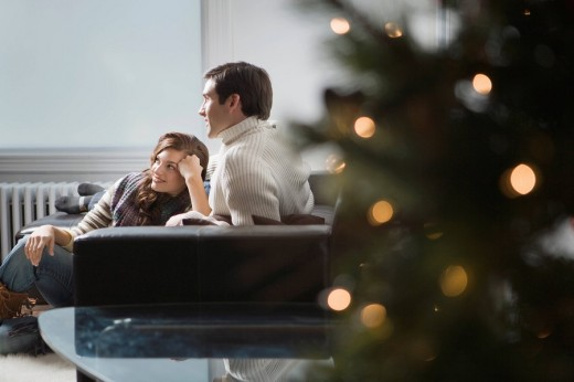 Portrait of young couple relaxing at home on Christmas, focus on background : Stock Photo