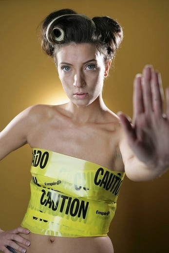 Young woman restrained by cordon tape, gesturing : Stock Photo