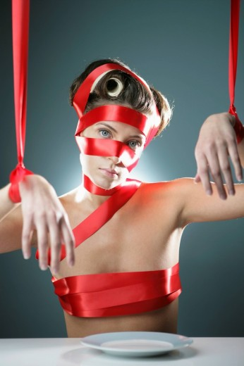 Young woman bound in red ribbon, portrait : Stock Photo