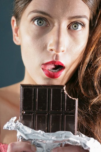Stock Photo: 1742R-15703 Young woman holding a large bar of chocolate, portrait
