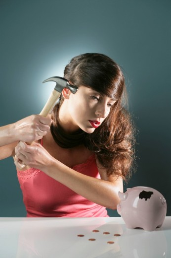 Young woman about to break a piggy bank with hammer : Stock Photo