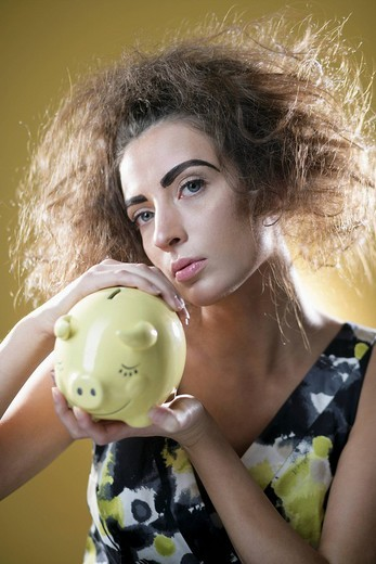 Stock Photo: 1742R-15717 Young woman holding piggy bank