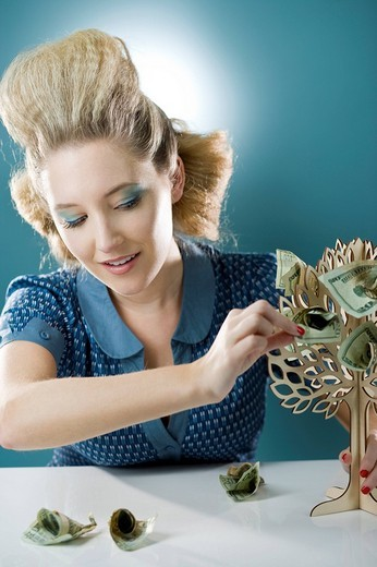 Young woman plucking money from toy money tree : Stock Photo