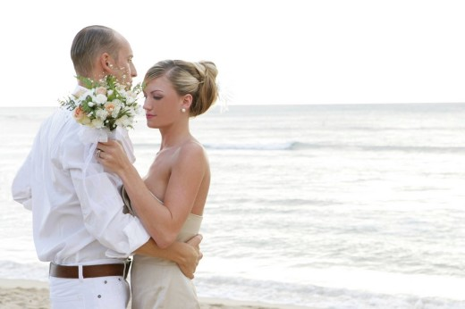 Wedding couple embracing on beach, bride holding bouquet : Stock Photo
