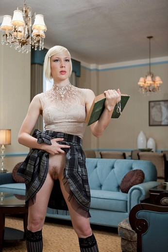 Portrait of blonde woman at home with book exposing herself : Stock Photo