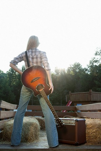 Stock Photo: 1742R-16736 Woman with guitar in back of truck