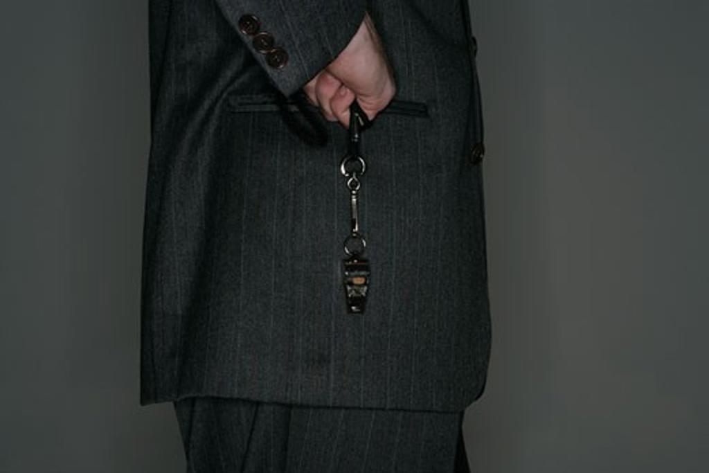 Man holding whistle, rear view : Stock Photo
