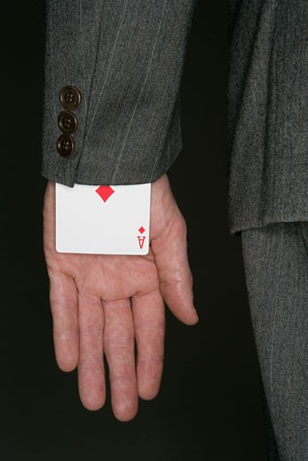 Businessman with playing card under his sleeve : Stock Photo