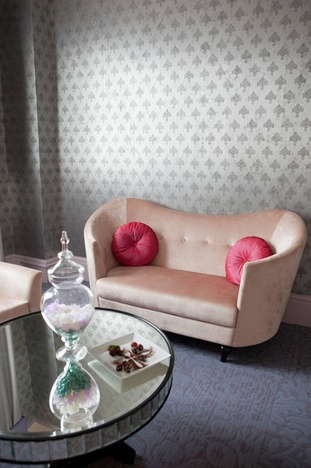 Coffee table and couch in a living room with wall to wall carpeting and wall paper : Stock Photo