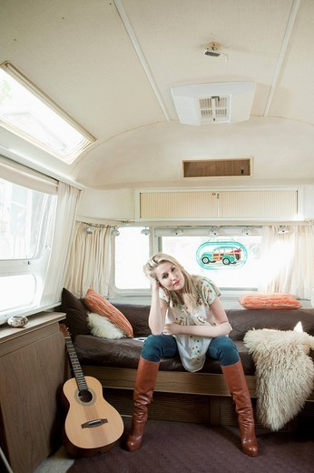 Mid adult woman with a guitar sitting in a caravan : Stock Photo