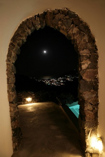 An arched door illuminated at night : Stock Photo