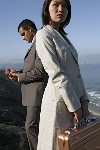 View of a man and a woman standing on a cliff. : Stock Photo