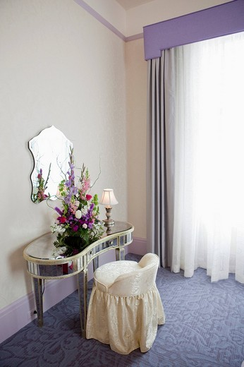 Mirror mounted on wall over bouquet and lit lamp on dressing table : Stock Photo