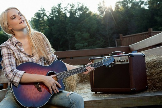 Woman with guitar in back of truck : Stock Photo