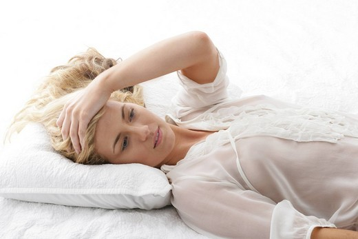 Stock Photo: 1742R-18880 Portrait of woman, laying on pillow,looking ahead