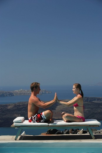 Young couple performing yoga on sun lounger : Stock Photo